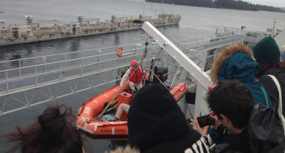 Students watching boat being lowered into water